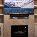 TV mounted over tiled Fireplace