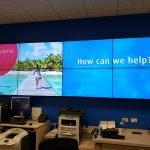 8 screens mounted in on large office wall