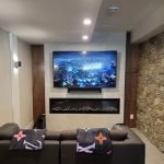 Large TV screen mounted on feature wall in TV room