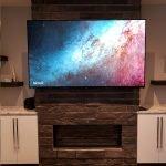 Large TV screen mounted on brick fireplace wall