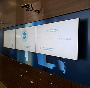 3 screens on wood wall with drawers beneath