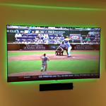 TV mounted on wall with speaker below and green backlighting