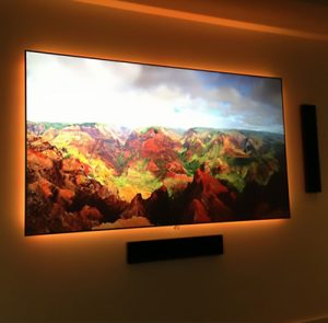 TV screen and speakers mounted on wall with background lighting