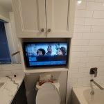 TV mounted over toilet in bathroom