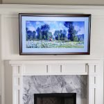 Picture frame TV mounted in wall unit with changing image