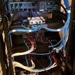 Back of networking cabinet with lots of cables