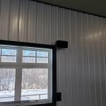 Speakers hung by window in a garage