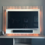 TV mounted on back of wall unit with backlighting